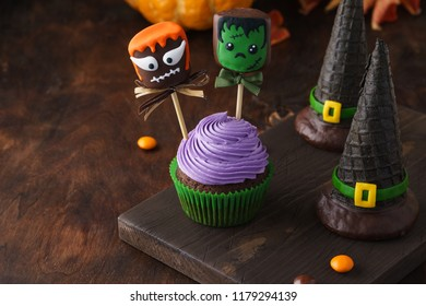 Festive Halloween cupcake decorated with cake pops or chocolate dipped marshmallow with funny monster faces and wafer witch hats. Dark background with space for text.