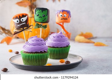 Festive Halloween cupcakes  with colored decorations. Marshmallow in chocolate with spooky monsters. Copy space, selective focus.