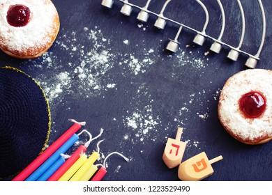 Festive Hanukkah flatlay: doughnuts with jam, dreidels, colorful candles, menorah and jewish bell on dark background. Selective focus.
