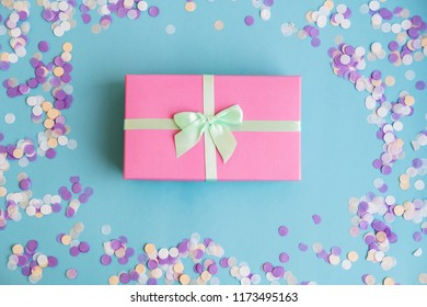 Festive holiday New Year and Christmas blue background with gift box, confetti. Concept of carnival, birthday, party. Flat lay. Top view
