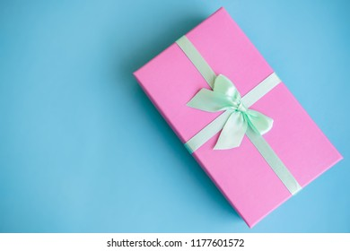 Festive holiday New Year and Christmas blue background with pink gift box. Concept of carnival, birthday, party. Flat lay. Top view