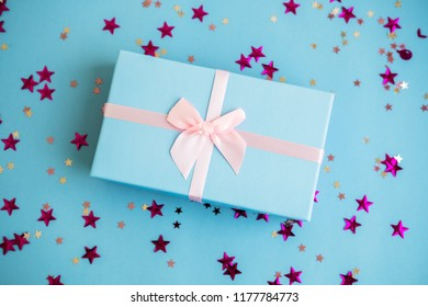 Festive holiday New Year and Christmas blue background with gift box, confetti, stars. Concept of carnival, birthday, party. Flat lay. Top view