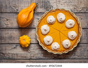 Festive Homemade Delicious Pumpkin pie with whipped cream made for Thanksgiving and halloween , top view. Autumn composition.