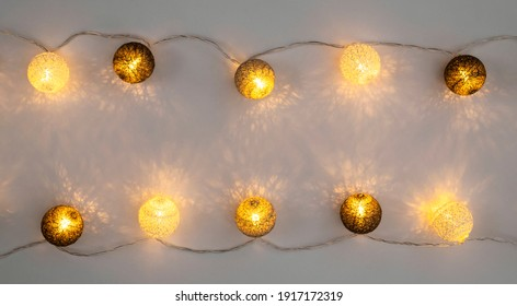 Festive included garland on gray background flat lay top view. Cotton Balls Garland. Round bulbs LED festoon electric garland. Twilight festive lighting backlight garland in children's room Decoration