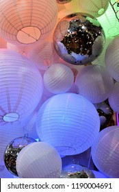 Festive indoor Christmas decorations.  Large paper lanterns, glass disco balls and reflection of Christmas lights.  Retail store display.  Millennial's party.