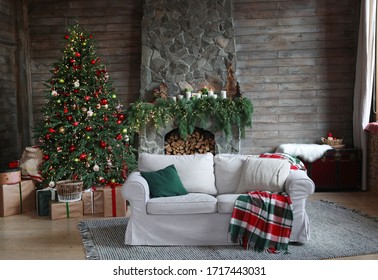 Festive interior with comfortable sofa and decorated Christmas tree
