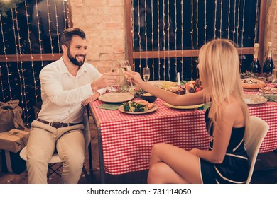Festive married youth enjoy with stemware of martini, so excited, elegant classy, checkered table cloth, december, garlands on windows, desktop setted with yummy tasty dishes, treats