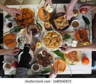 A festive meal at a white wooden table with homemade cakes.Meeting friends who have healthy natural food. Flat position of the table with hands of food and the people holding the food.