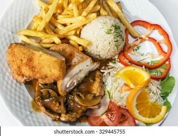 Festive menu of chicken breast stuffed with ham and cheese with rice, fries and pork with sauce and mushrooms.