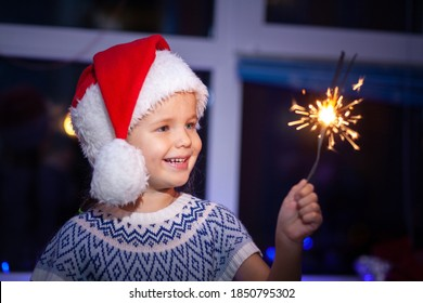 Festive Merry Christmas sparklers. Portrait of a cute little girl holding sparklers, new year 2021, winter holiday.
