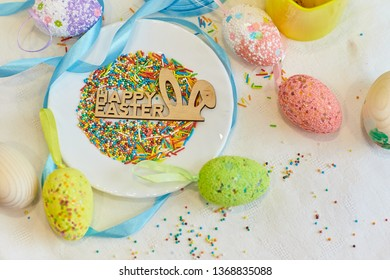 Festive mess while preparing for a happy Easter holiday. Decorative handmade Easter eggs lying near the plate with powder for Easter cake. Top view shot close up on white background.