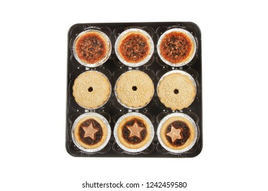 Festive mince pies in a plastic tray isolated against white