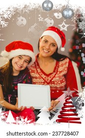 Festive mother and daughter showing tablet screen against christmas themed frame with decoration