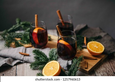 Festive mulled wine served with orange and a cinnamon stick.