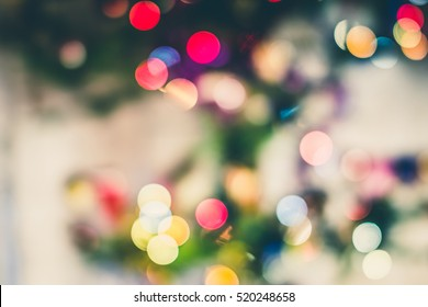 Festive New-year background with bokeh from Christmas tree lights glowing. Blurred colorful circles on light holiday background