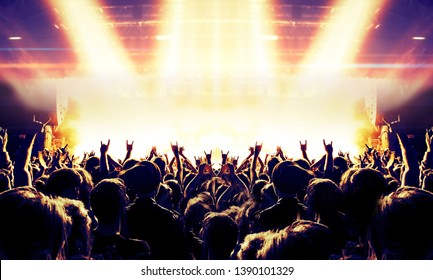 Festive night concert crowd clapping in front of a band stage
