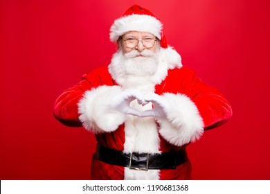 Festive noel seasonal kind positive stylish aged Santa look at camera make nice smile and shape heart with fingers hands isolated on bright red background