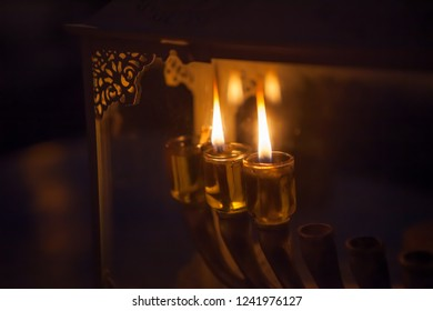 Festive oil candles burning in a decorative glass box, Chanukkah concept, background with copy space
