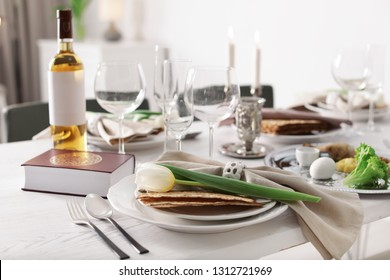 Festive Passover table setting with Torah at home. Pesach celebration