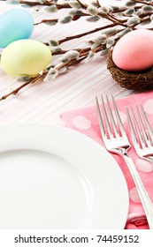 A festive pastel pink table setting is decorated for Easter with traditional dyed eggs and pussy willows leaving ample copy space on a white plate