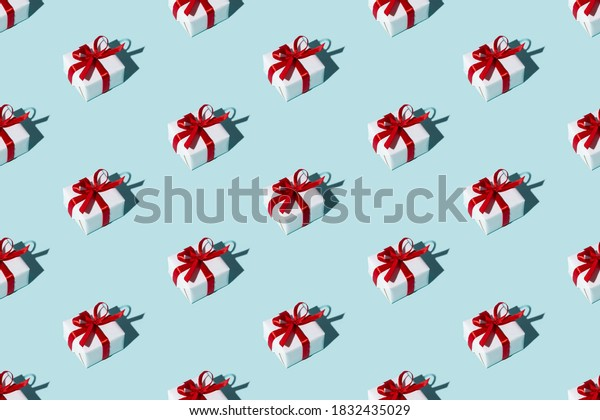 Festive pattern. Blue seamless background. Long-distance gift. Holiday present. Symmetrical arrangement of white boxes with red ribbon bows isolated on light color.