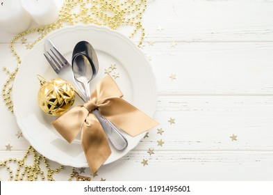 Festive place setting for christmas dinner on white rustic background. Christmas table setting with gold decorations on wooden table. Holiday Decorations. Top view. Copy space.