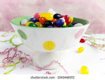 A festive polka dot bowl filled with colorful jellybeans on white with a pink background.  Pink and green Easter grass is scattered on the surface.