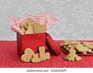 A festive red box filled with dog cookies in bone and heart shapes.