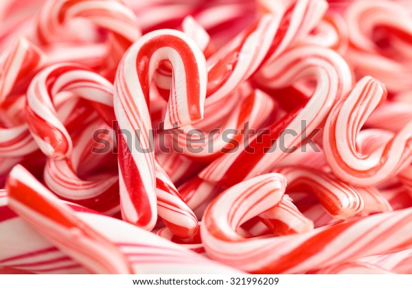 Festive red and white peppermint candy canes  background.