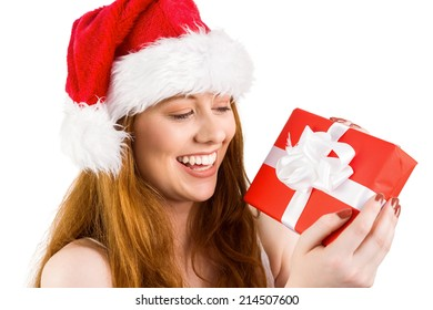 Festive redhead holding a gift on white background