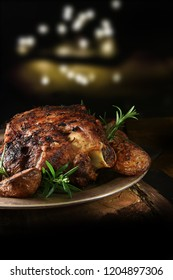 Festive roasted leg of lamb slow roasted with garlic, red onion and rosemary herbs, shot against a dark, festive background with generous accommodation for copy space.