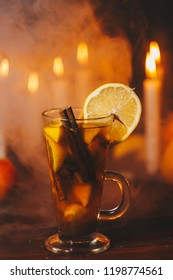 a festive rum punch in smoke on Halloween day. drink with almond, apple, lemon and cinnamon stick. candles and a jack-o-lanterm in the background. mulled wine warming drink.Thanksgiving Day