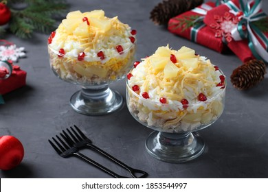 Festive salad with chicken, pineapple, cheese and eggs in portioned bowls on dark gray background. New Year still life. Closeup