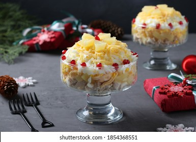 Festive salad with chicken, pineapple, cheese and eggs in portioned bowls on dark gray background. Horizontal format