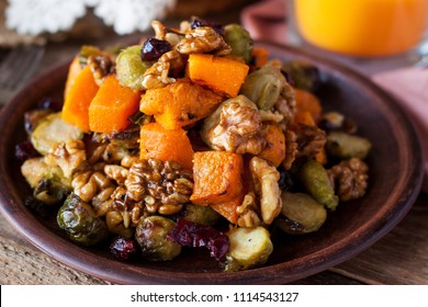 Festive salad with roasted brussels sprouts, butternut squash, pecans and cranberries glazed with honey and cinnamon sauce.