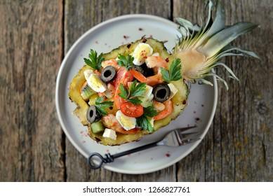 Festive salad of shrimp, kiwi, olives, soft cheese, quail eggs, cherry tomato in pineapple plates. Christmas background.