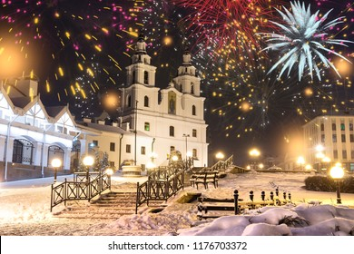 Festive salute in night Minsk for Christmas and New Year. Celebrating New Year in Belarus. Fireworks and salutes, night lights of city on main Orthodox church of holy spirit in center of city