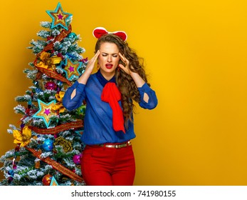 Festive season. Portrait of stressed elegant woman near Christmas tree on yellow background