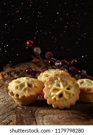 Festive, seasonal, traditional Christmas mince pies with sugar frosting shot against a dark, creatively lit rustic background with generous accommodation for copy space.