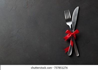 Ensemble festif de couteaux et de fourchette avec noeud satiné rouge, arrière-plan béton en ardoise de pierre noire, vue de dessus, espace pour copie.