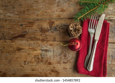 Festive setting for christmas holiday dinner. Vintage cutlery on the red napkin and christmas decoration on the old wooden background with copy space