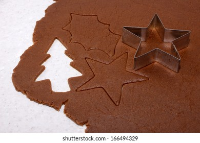 Festive shapes and star cookie cutter on gingerbread cookie dough