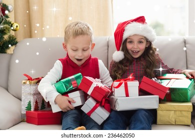 Festive siblings surrounded by gifts against snow