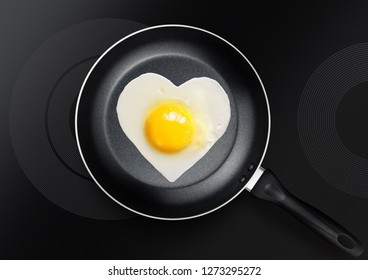 festive snack made of fried egg in the form of heart on frying pan for Valentine's Day