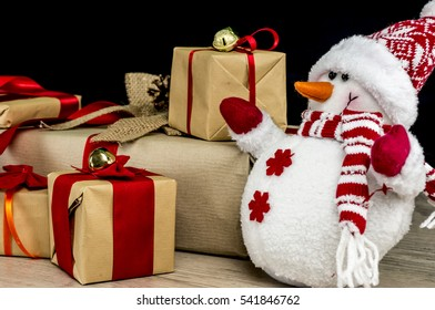 Festive snowman in front of Christmas presents