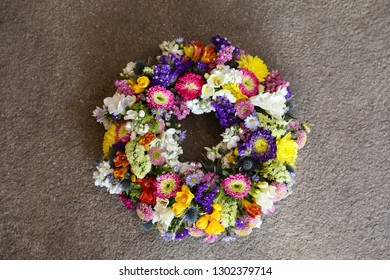 Festive Spring Easter Decor. Beautiful wreath of chrysanthemums, sea lavender, freesia, eryngium flowers in happy colors on a gray concrete background. Horizontal.