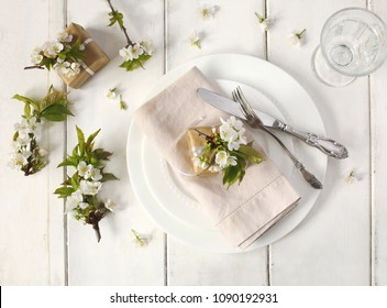 Festive spring table setting with pear blossom flowers, top view