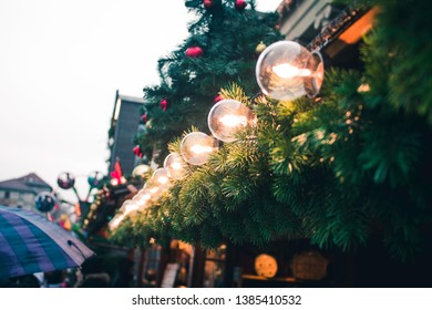 Festive spruce branches with Christmas lights. Christmas fair, Christmas market. Close up. Winter.