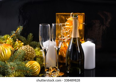 Festive Still Life of Bottle of Champagne with Elegant Glasses on Black Background with White Candles, Gold Wrapped Gifts and Evergreen Branches Decorated with Gold Christmas Balls and Tinsel