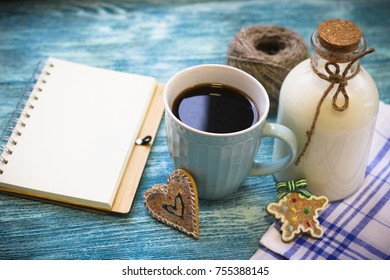 Festive still life with a bottle of milk, a cup of freshly brewed fragrant coffee, biscuits, a skein of yarn, a notepad, a checkered tablecloth on a turquoise wooden table, a light background